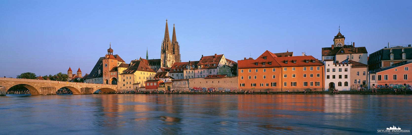 Die Silhouette der Altstadt von Regensburg als Panorama vom Ufer der Donau. Wie in vielen Städten der Welt, wird der Uferbereich in den Sommermonaten gern für einen abendlichen Sundowner genutzt, so auch hier in der bayrischen Metropole Regensburg.